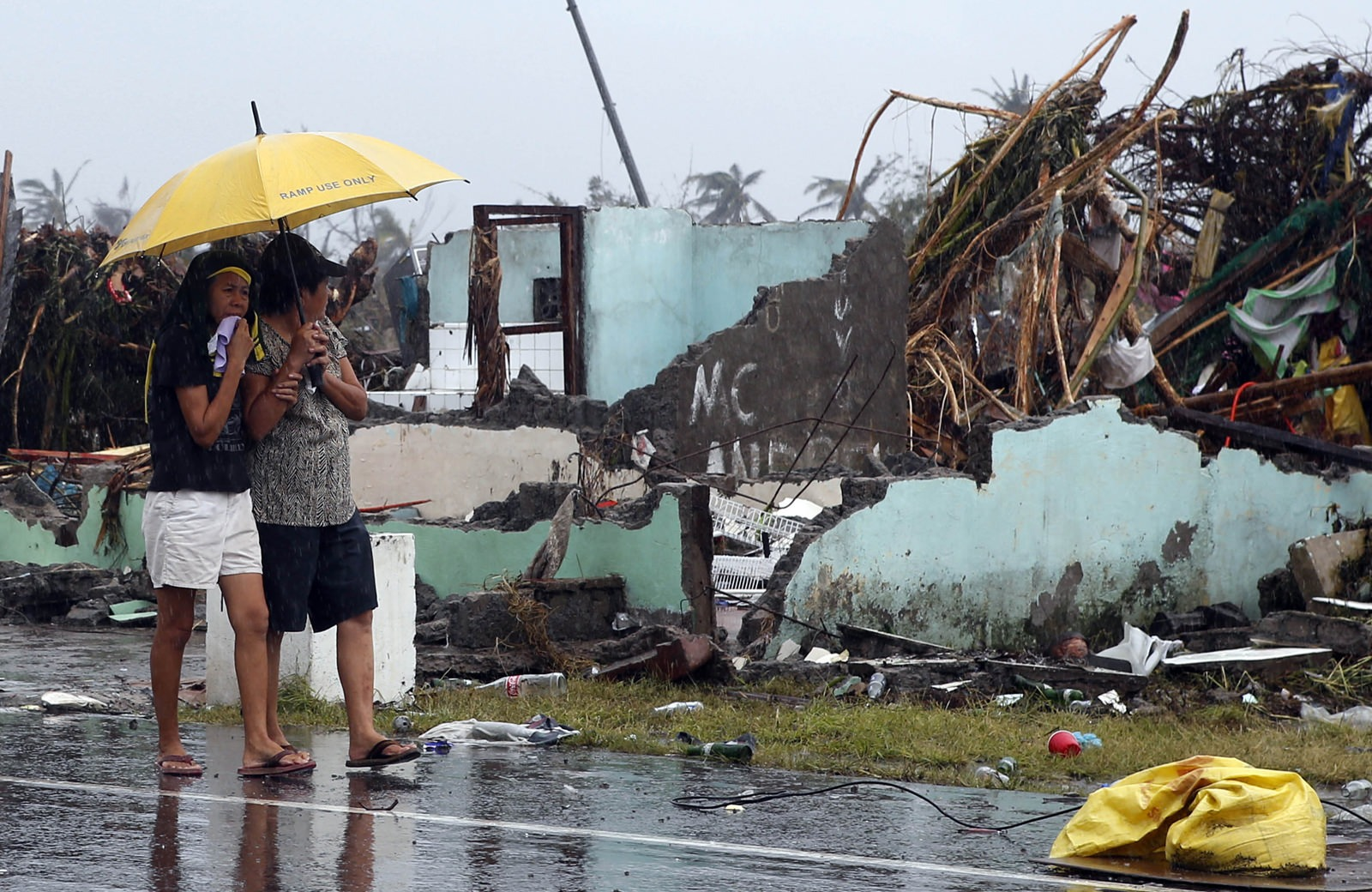 Women share an umbrella as they look at the remains of a house destroyed after Typhoon Haiyan hit Tacloban city in central Philippines